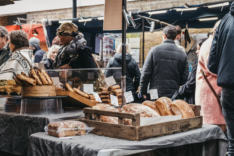 People buying fresh bread and pastries from a market stall at Greenwich Market, London's only market set within a World Heritage Site. Adult Food Business People Day Group Of People Artisanal Food And Drink Artisan Fresh Bread Bread Retail  Group Stack Retail Display Real People Greenwich Market Greenwich Freshness Take Away Market Stall Market Food And Drink Uk London Retail  Women For Sale Occupation Small Business