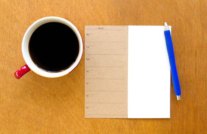 Directly Above Shot Of Black Coffee With Paper And Pen On Table