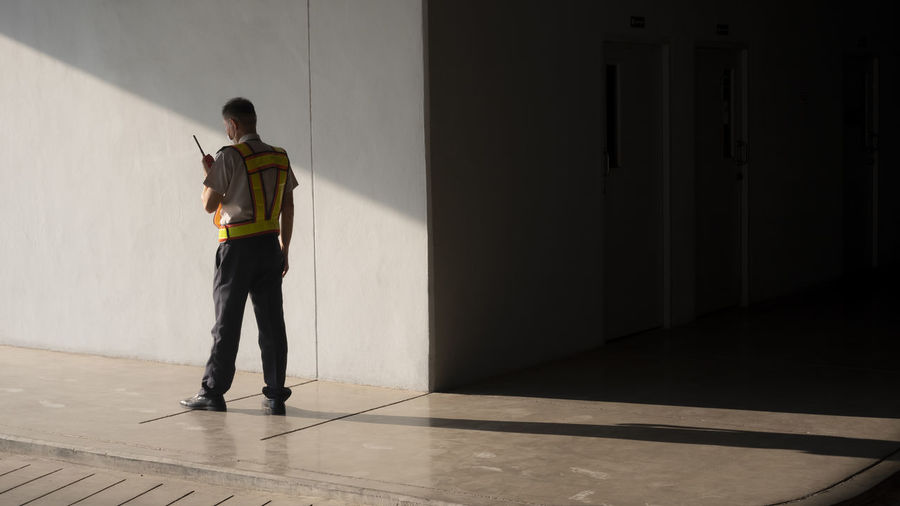 Rear view of engineer standing in corridor at warehouse