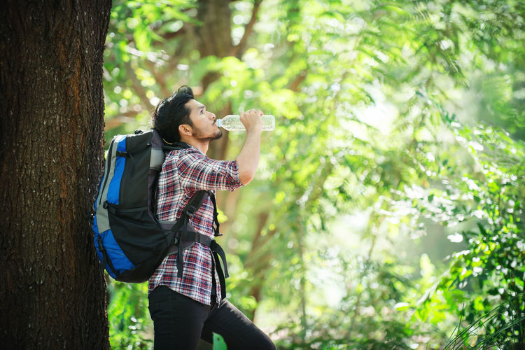 Male Hiker Drinking Water While Carrying Backpack In Forest