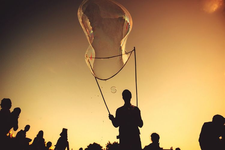 Low angle view of silhouette man blowing giant bubble from wand during sunset