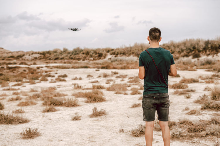 Rear view of young man flying drone standing on field