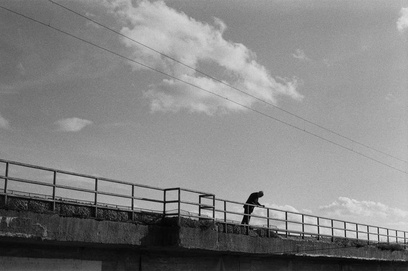 a man leaning over a bridge Blackandwhite Outdoors Film Film Photography 35mm Film Ilford Streetphotography Street Outdoor Photography Water Sea Men Standing Railing Sky Architecture
