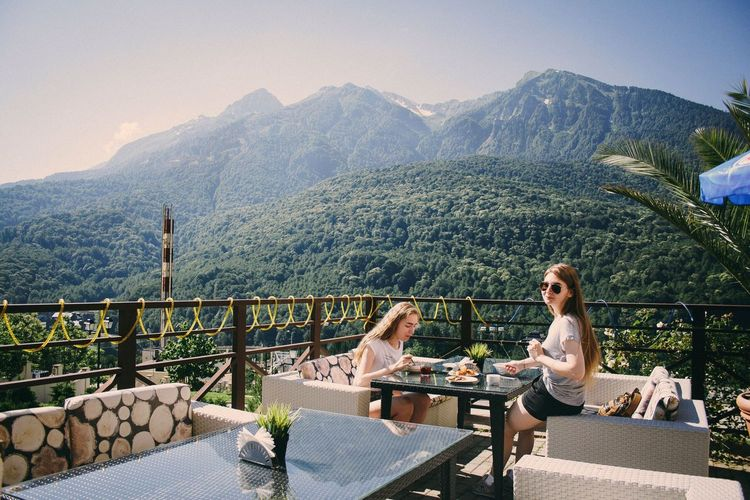 Architecture Nature Real People Women Sitting Relaxation Table Day Outdoors Food And Drink Mountain Russia Sochi Seat Adult Beauty In Nature Lifestyles Young Adult Two People Young Women Mountain Range Connected By Travel Leisure Activity Scenics - Nature Perspectives On Nature