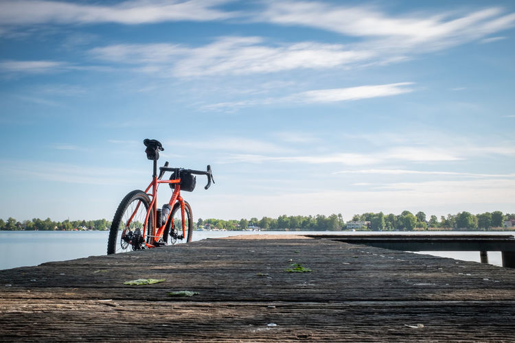 Bicycles riding bicycle on shore against sky