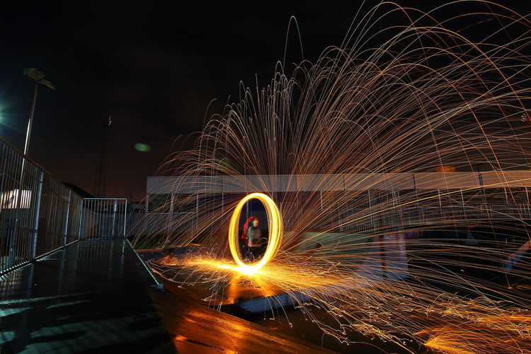 Wire Wool spinning Motion Illuminated Long Exposure Night Wire Wool Nature Outdoors Spinning Glowing Blurred Motion Sparks Light Painting Speed Burning One Person Architecture Fire Pattern Real People Light Trail Built Structure Firework Display Firework Light