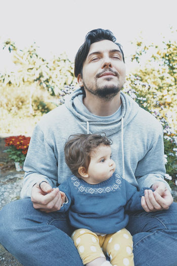 Father and daughter sitting outdoors