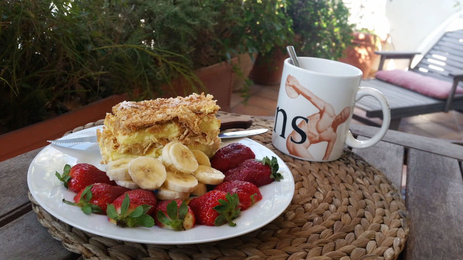 Close-up of fresh breakfast served with coffee on table in back yard