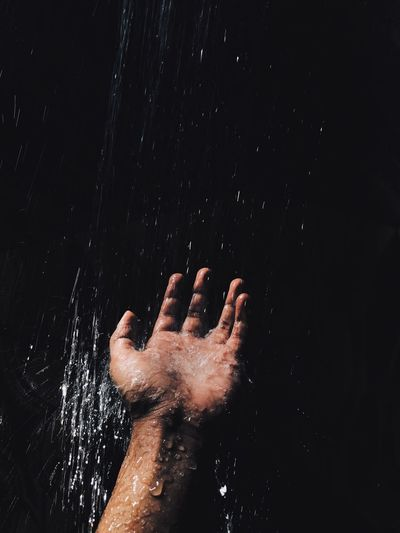 Water splashing on hand against black background