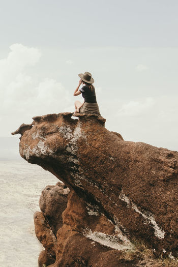 Higher. Exploring Kenya Maasai Mara Rear View Adult Cloud - Sky Day Explore Full Length Hiking, Mountains, Adventure Leisure Activity Lifestyles Nature One Person Outdoors Real People Rock Rock - Object Rock Formation Side View Sitting Sky Solid Women Go Higher The Traveler - 2018 EyeEm Awards