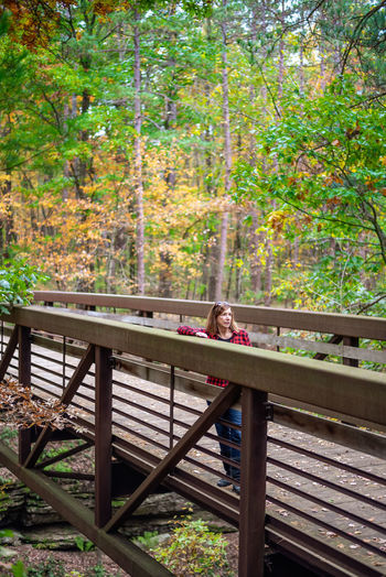 Portrait of a man relaxing on railing in forest