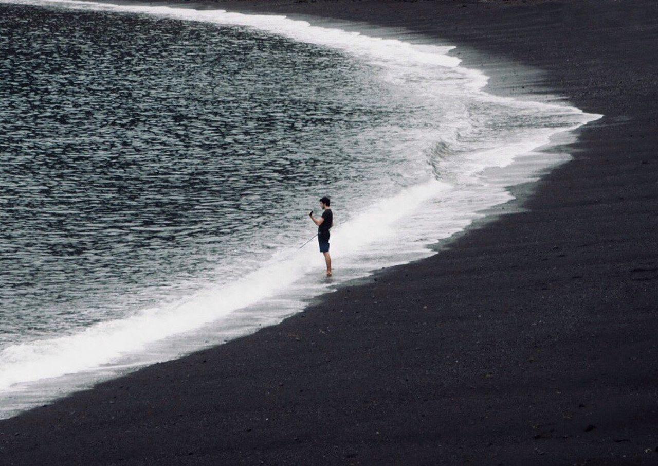 FULL LENGTH OF MAN STANDING ON SHORE AT BEACH