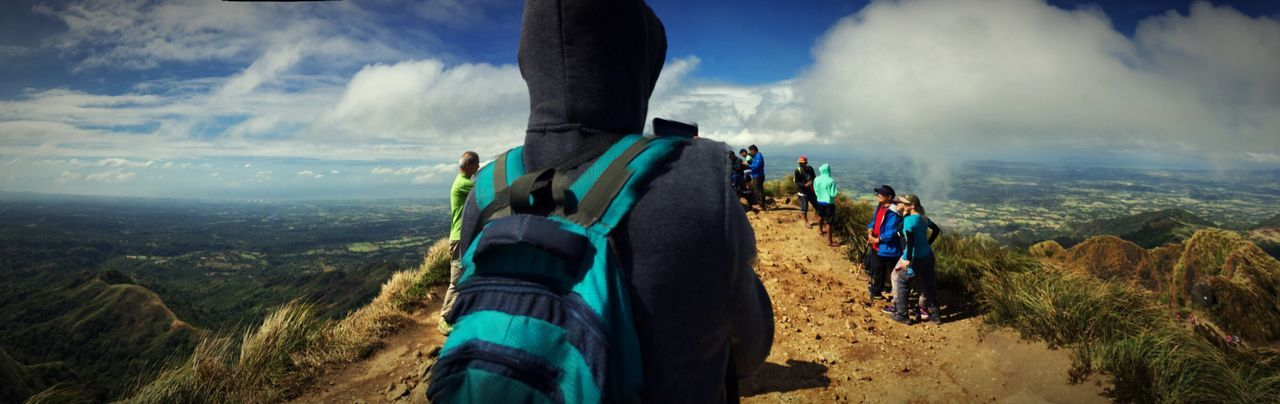 Low section of people on mountain against cloudy sky