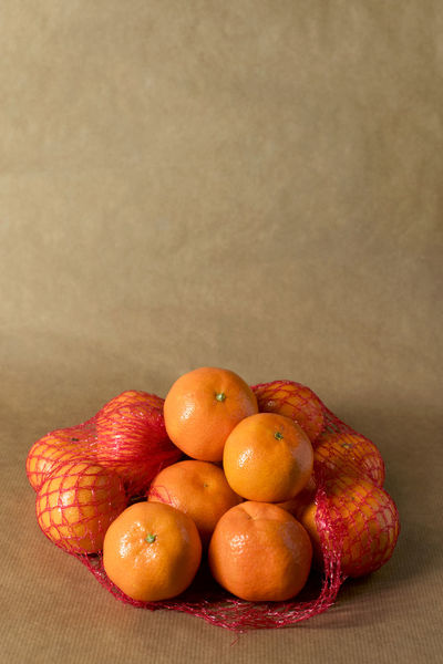 Clementines in nets on brown paper - supermarket packaged food Citrus  ClementinesDay Freshness Snack Supermarket Brown Brown Paper Citrus Fruit Clementine Clementines Fruit Healthy Healthy Food Ingredient Mandarins Monochromatic Monochrome Mood Night Obst Orange Color Packaging Pile Still Life
