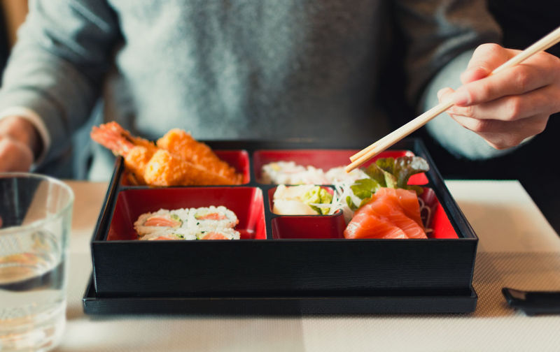 adult eat sushi at Japanese restaurant Sushi Human Hand Food And Drink Food Chopsticks Hand Asian Food Freshness Rice Holding Tray Healthy Eating Japanese Food Rice Meal Restaurant Lunch Box Adult Sea Food Chinese Food Freshness Indoors  Asian  Japanese  Table