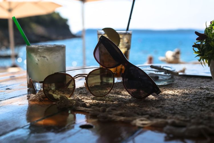 Close-up of sunglasses on table at beach