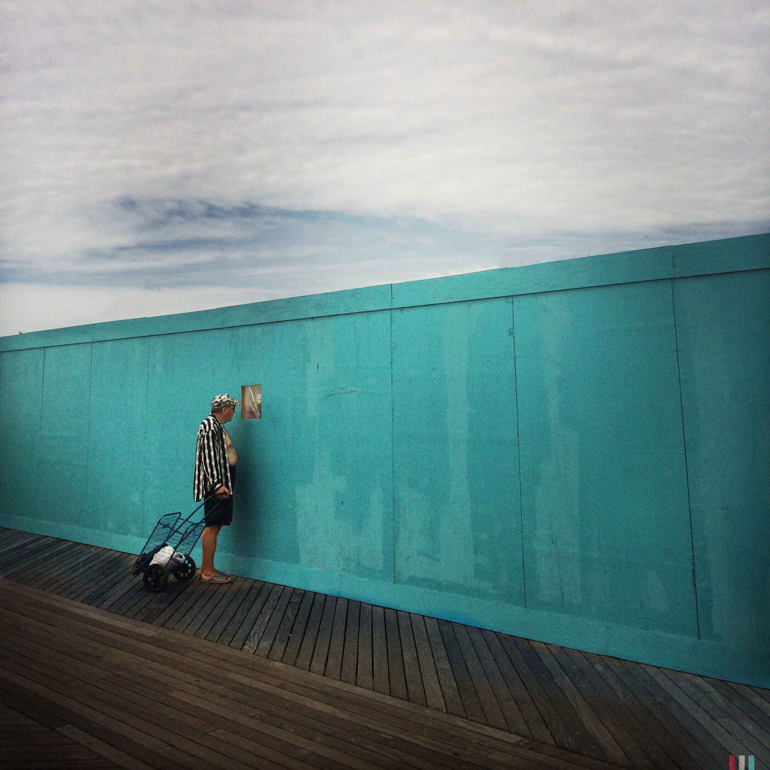 sky, cloud - sky, men, sea, built structure, lifestyles, architecture, horizon over water, full length, leisure activity, building exterior, cloud, cloudy, bicycle, transportation, rear view, water, person
