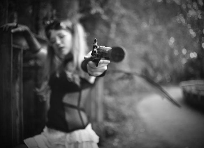 Woman shooting with handgun outdoors