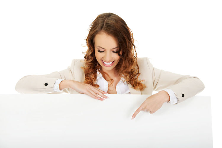 Smiling businesswoman pointing on placard against white background