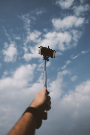 Close-up of hand holding monopod against sky