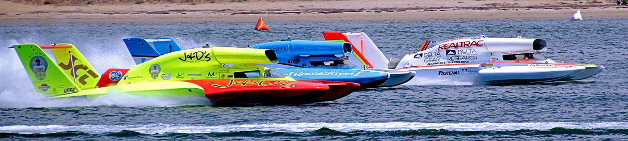 "Unlimited Hydroplanes are fast boats using jet aircraft engines and capable of more than 320 km/h (200 mph) on the straights and running average lap speeds of 209–266 km/h (130–165 mph). They are 8.5–9.1 metres (28–30 ft) in length and weigh a minimum of 3,060 kilograms (6,750 lb). Races are run on an oval course marked by inflatable buoys. Races begin with a ""running start"" meaning they must all be moving in their respective positions as the cross the start line and if they are in the position they are supposed to be in, the Starter gives them the Green Flag and they are off racing. During the race if the Starter gives them a Yellow flag it means to slow down and proceed with caution and no one can pass another boat, (hold your current position). If the Starter waves a Red flag, the race is stopped and everyone should stop where they are. Once the final lap is over and the lead boat passes the Finish Line, the Starter gives them the Checkered Flag, declaring them the Winner and the race over. Boat Racing, Speed Boats, Power Boats, Inland Waterways, Bay, Harbor, Planing, Hydroplace Boat, Unlimited Boat, Jet, Spry, Race Course, Day Hydroplane Race, Speed Boats, Boat Racing, Powerboats, Thunderboats, Boat Races, Unlimited Hydroplanes, Pit Area, Mission Bay, San Diego, California, Bayfair, Outdoors Water"