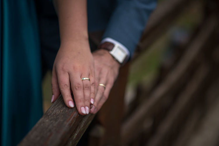 Cropped hands of couple on railing