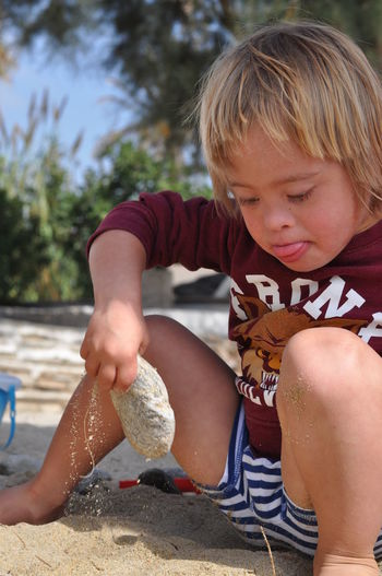 Beach Blond Hair Boys Casual Clothing Childhood Close-up Cute Day Elementary Age Focus On Foreground Full Length Happiness Leisure Activity Lifestyles One Person Outdoors Playing Real People Sand Sand Pail And Shovel