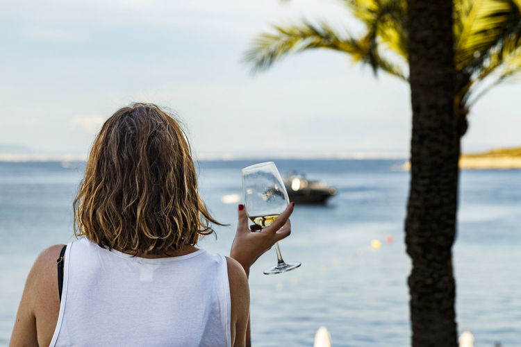 Woman having wine at beach against sky