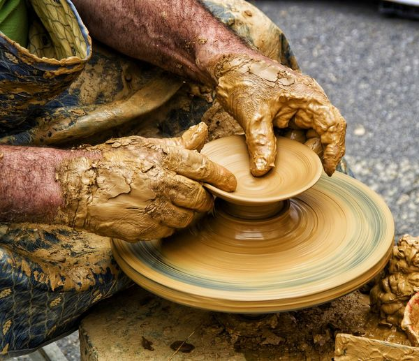 Cropped Image Of Potter Shaping Earthenware On Pottery Wheel