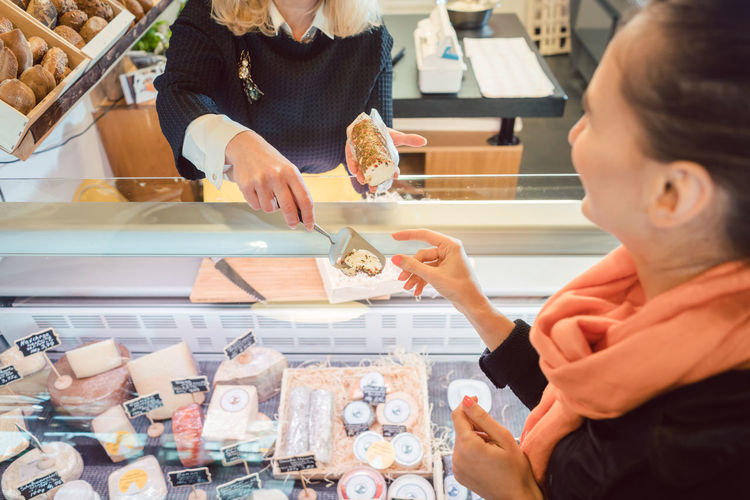 Midsection of woman having food at store