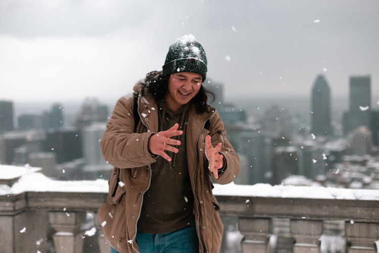 Smiling young woman standing against snow during winter