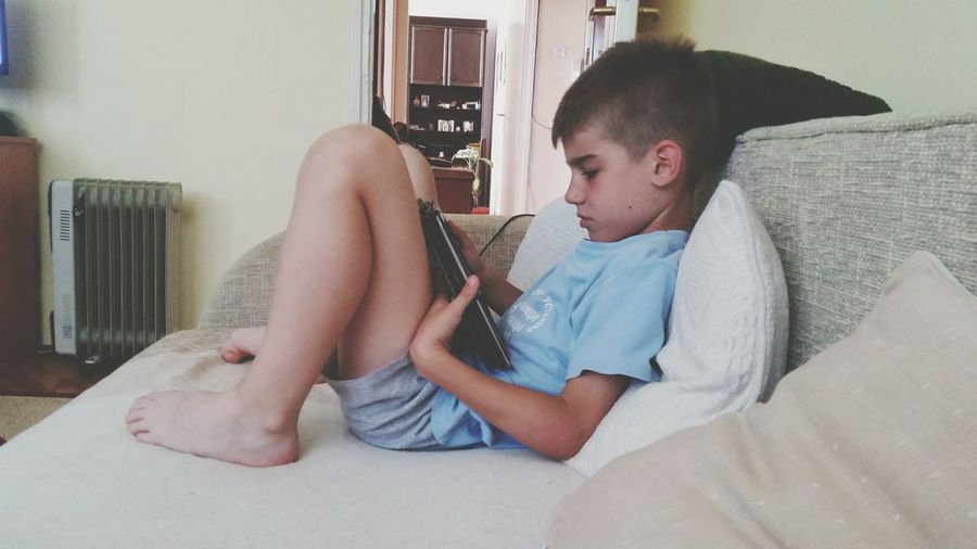 Side view of boy using digital tablet on sofa at home
