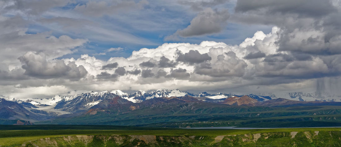 View from the Denali Highway in Alaska. Alaska Glacier Sense Of Scale Beauty In Nature Cloud - Sky Field Grass Land Landscape Mountain Mountain Range Nature No People Outdoors Range Scenics - Nature Sky Snowcapped Mountain Panoramic Dramatic Sky Storm Cloud