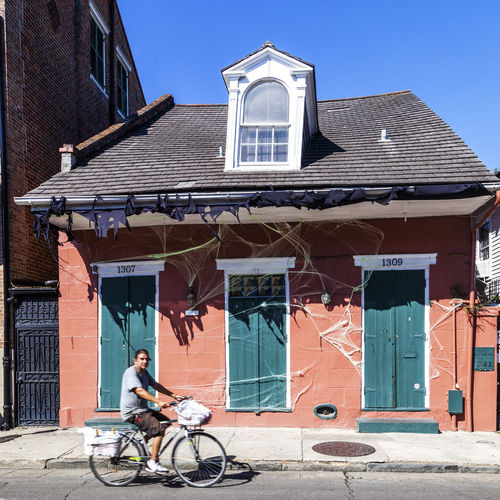 Man riding bicycle against building on sunny day
