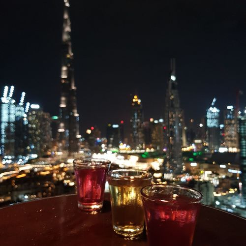 Wine glass of illuminated buildings in city against sky at night
