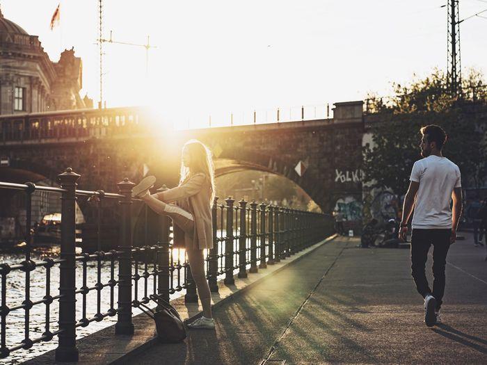Rear view of man on bridge against sky in city