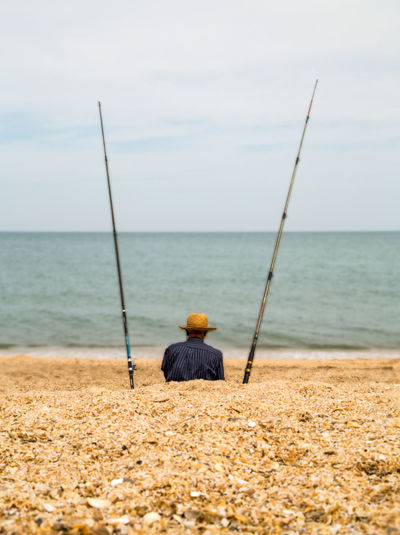 Man with fishing rods sitting at beach against sky