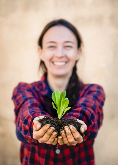 Portrait of a smiling young woman holding plant