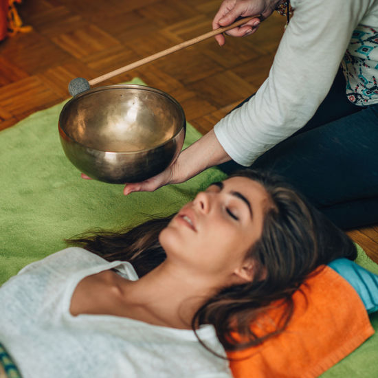 Midsection Of Therapist Playing Rin Gong By Young Woman At Spa