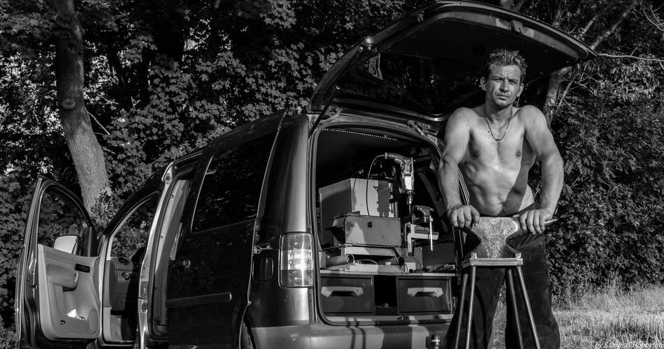 Portrait of shirtless man holding anvil on table against vehicle