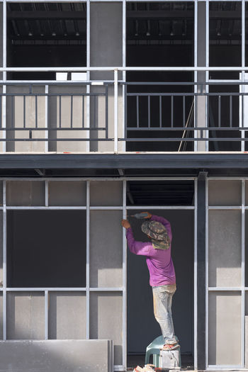Woman standing by window against building