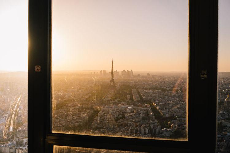 Cityscape seen through window during sunset