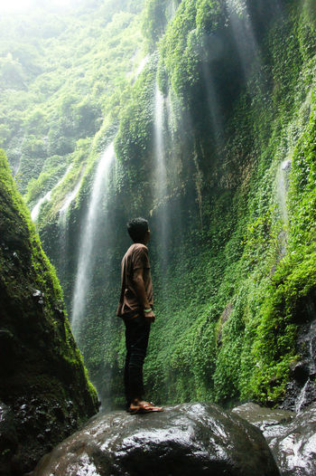 Full length of man looking at waterfall in forest