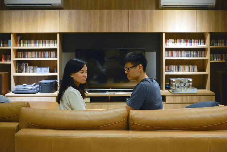 Angry Asian couple fighting in front of TV in living room at night Adult Book Bookshelf Cabinet Day Fighting Friendship Indoors  Leisure Activity Library Lifestyles Living Room Men Night People Real People Sitting Sofa Togetherness Tv Two People Watching Young Adult
