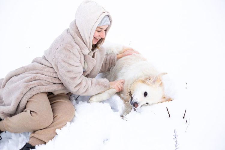 Man with dog on snow during winter
