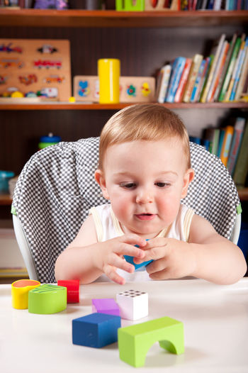 Cute baby boy playing with toys on table at home