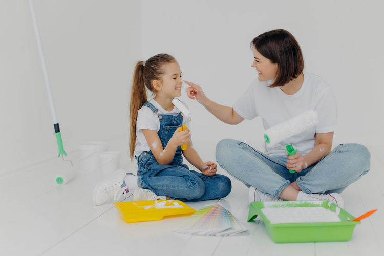 Woman applying paint on daughter nose while sitting at home