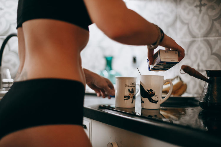 Midsection of woman preparing drink