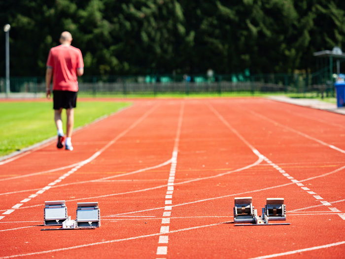 Sportsman walk on the running tracks after training. course. starrting blocks at athletics stadium