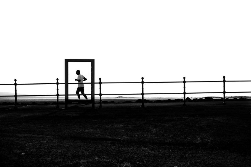 Silhouette man running on footpath against clear sky